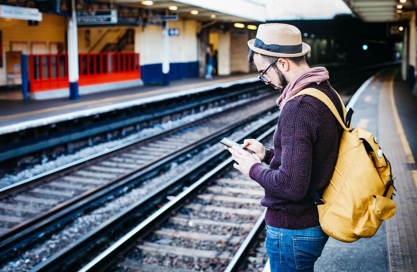 man using a mobile on station platform
